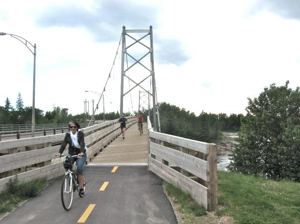 Suspension bridge alongside busy boulevard accommodates cyclists and joggers in Dolbeau-Mistassini.