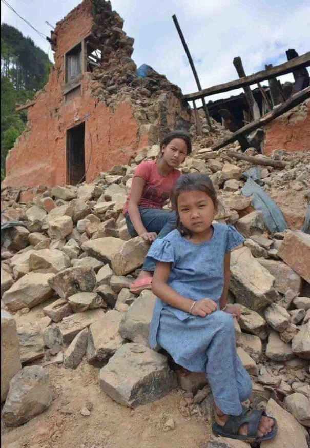 TWO GIRLS IN RUBBLE OF THEIR HOUSE