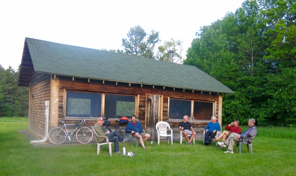 Happy campers relax outside building in yurt zone